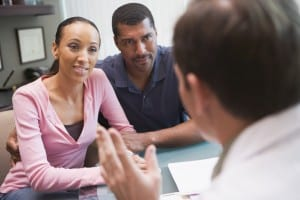 Couple having discussion with doctor in IVF clinic sitting at desk